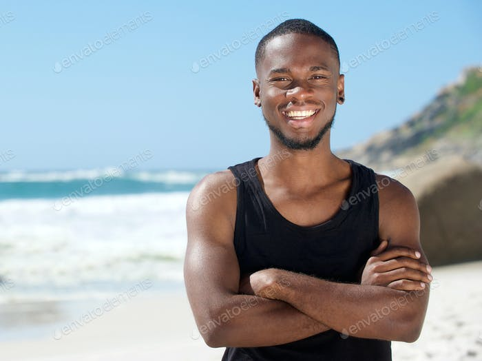 Handsome cheerful man smiling at the beach