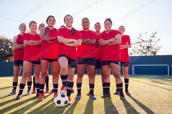 Portrait Of Smiling Womens Football Team Training For Soccer Match On Outdoor Astro Turf Pitch