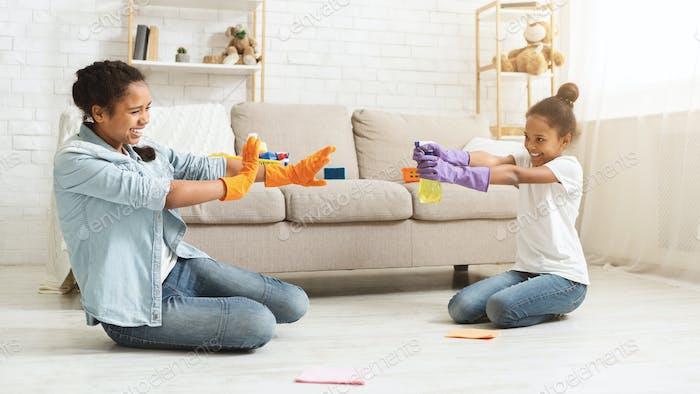 Playful girls having fun during cleaning home