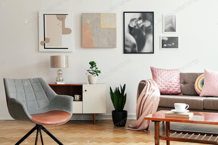 Grey armchair in living room interior with lamp and plant on cab