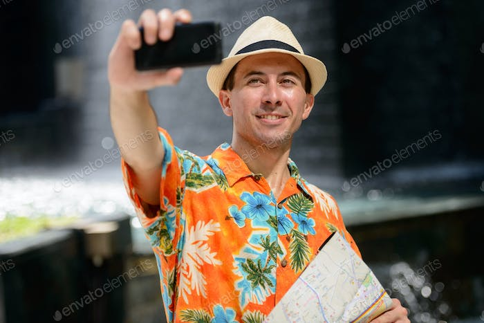 Happy young handsome tourist man taking selfie in the city outdoors