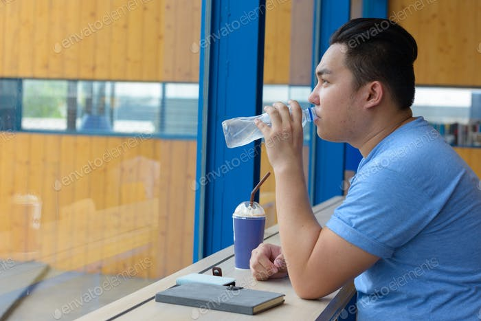 Young overweight Asian man drinking water at the coffee shop