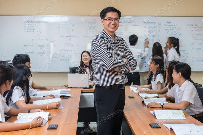 Portrait of Asian teacher standing when Giving Lesson to group of College Students