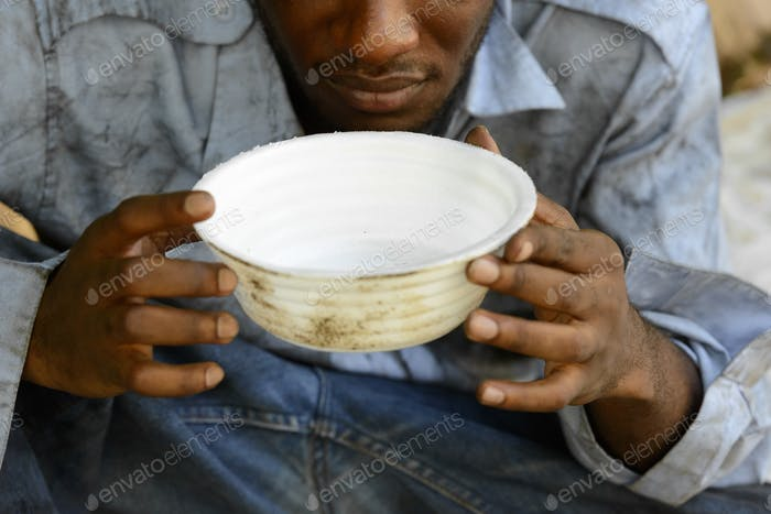 Hands of young homeless African man begging for food