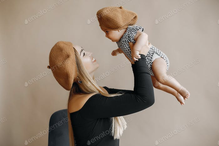 Elegant mother with cute little daughter in a studio