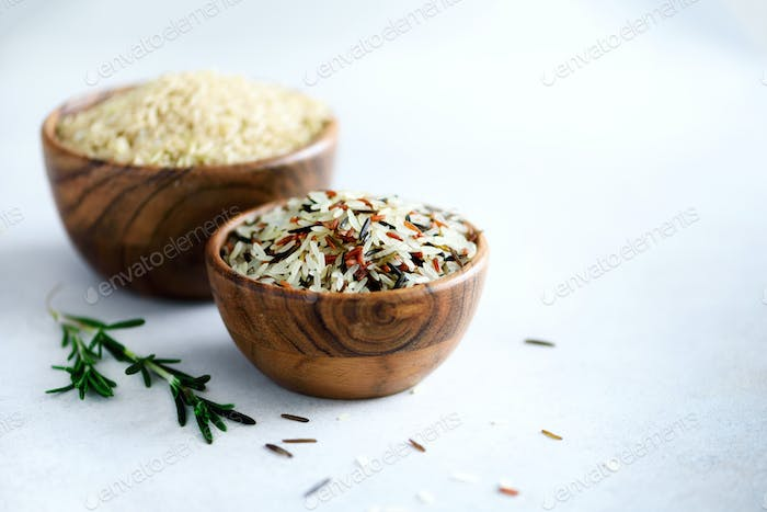 Raw organic brown rice in wooden bowl and rosemary on light concrete background. Food ingredients