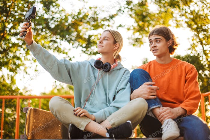Young skater boy and girl recording new video while spending tim