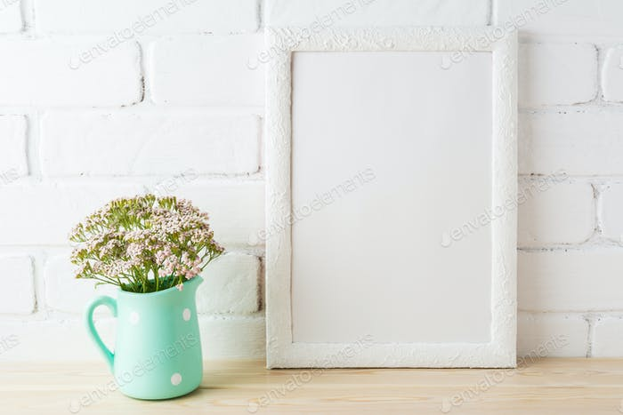 White frame mockup with soft pink flowers near exposed bricks