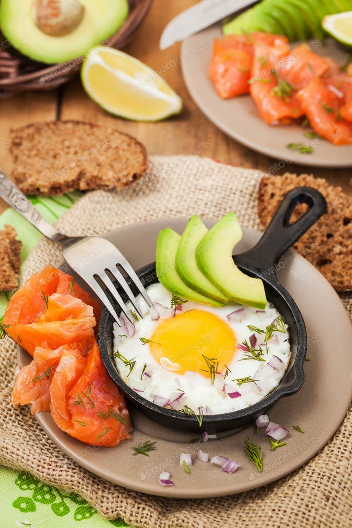 Fried egg, avocado and smoked salmon in frying pan