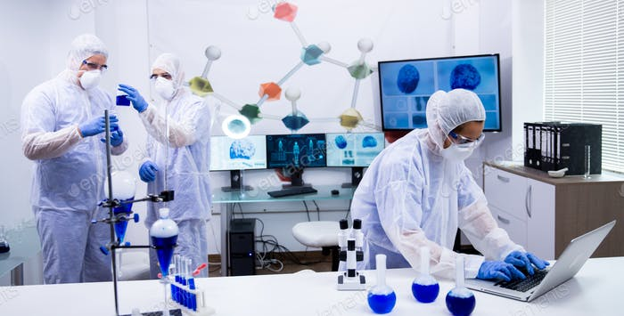 Team of scientist in protection equipment working in a modern research laboratory