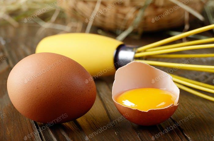 Raw organic brown chicken broken eggs with yolk wicker basket an