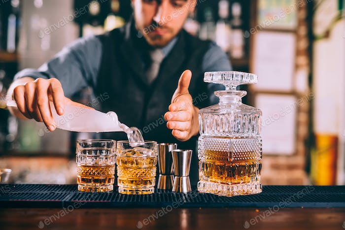 Portrait of bartender adding ice to delicious alcoholic whisekey cocktails
