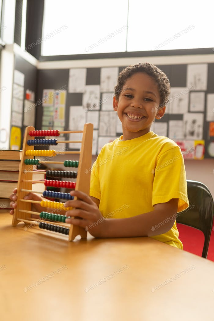 Happy smiling schoolboy with abacus looking at camera in a classroom at elementary school