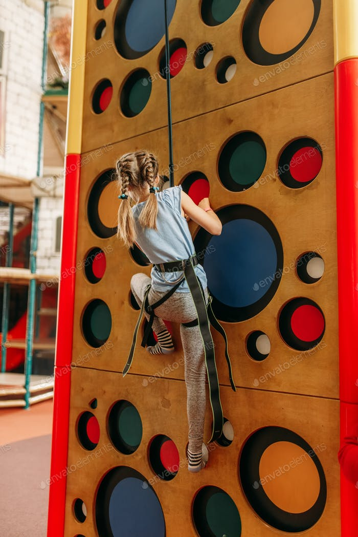 Funny girl climbing walls in children game center