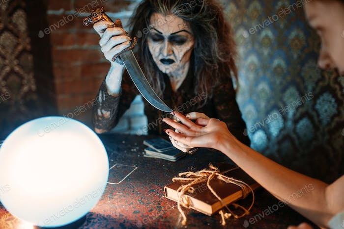 Scary witch with knife, spiritual seance