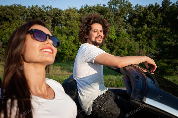 Gorgeous young dark-haired woman in sunglasses with curly young man are sitting in a black cabriolet