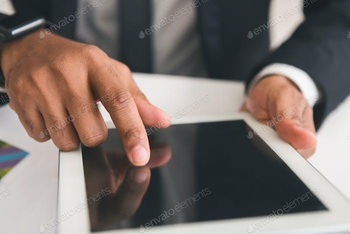 Moderner Geschäftsmann mit digitalem Tablet am Arbeitsplatz