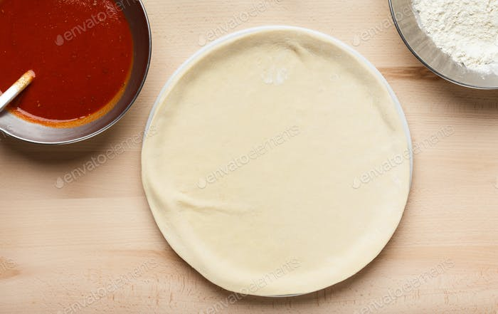 Pizza preparation. Raw pizza base and sauce in bowl