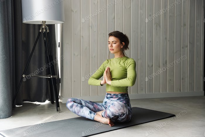Photo of focused young woman meditating while doing yoga exercises