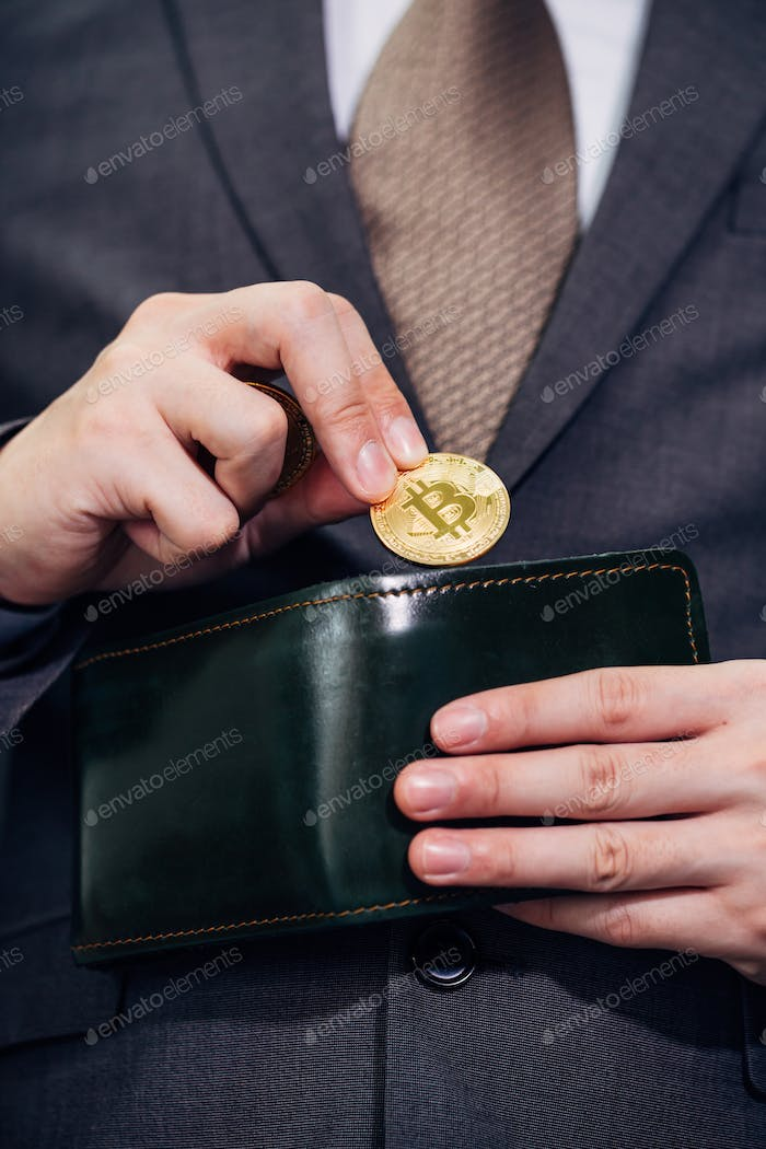 Close-up of businessman with wallet receiving and paying by bitcoin or cryptocurrency