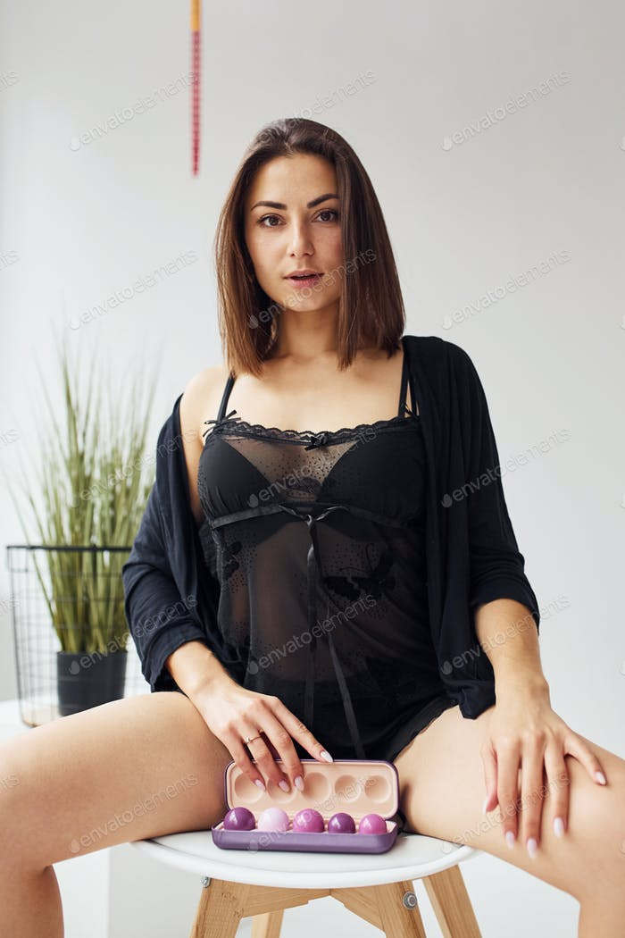 Woman in black sexy clothes, with vaginal balls and imbuilding tools in the room
