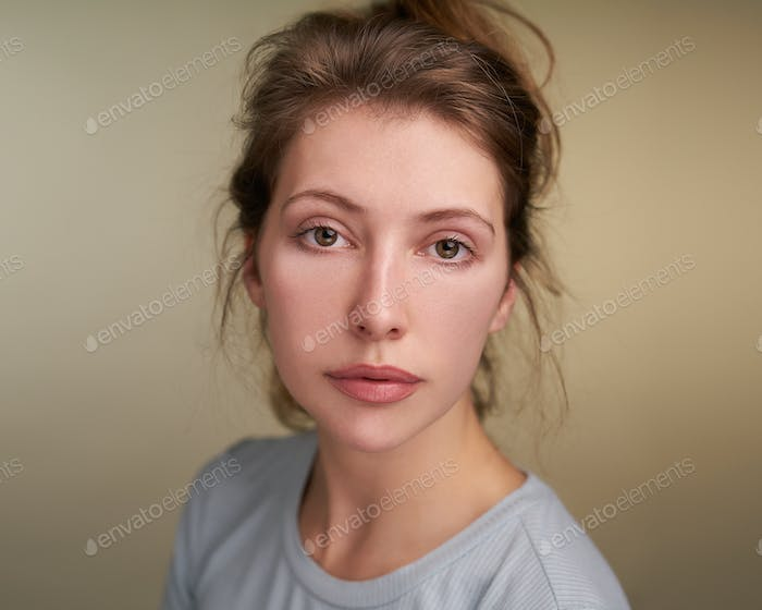Portrait of young woman on brown backdrop