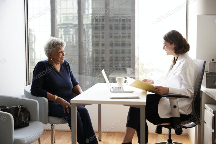 Senior Woman Having Consultation With Female Doctor In Hospital Office
