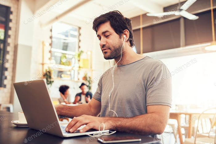 Young man with earphones using laptop at a cafe