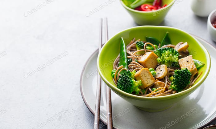 Soba noodles with vegetables and fried tofu in a bowl. Copy space. Grey background.