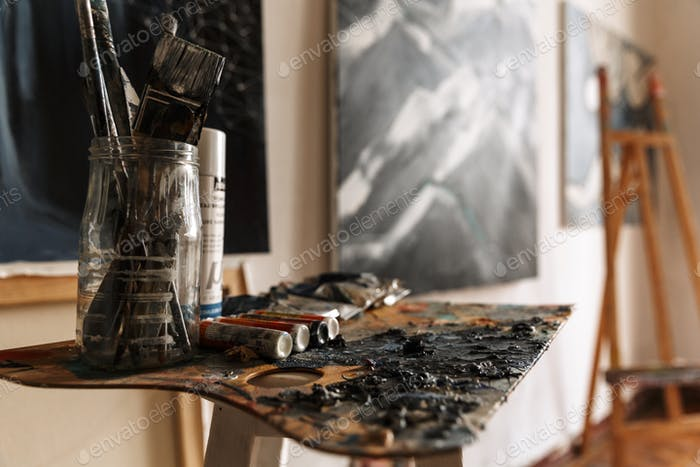 Image of artist workplace with painting tools and artworks on wall