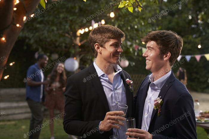 Gay Couple Celebrating Wedding With Party In Backyard