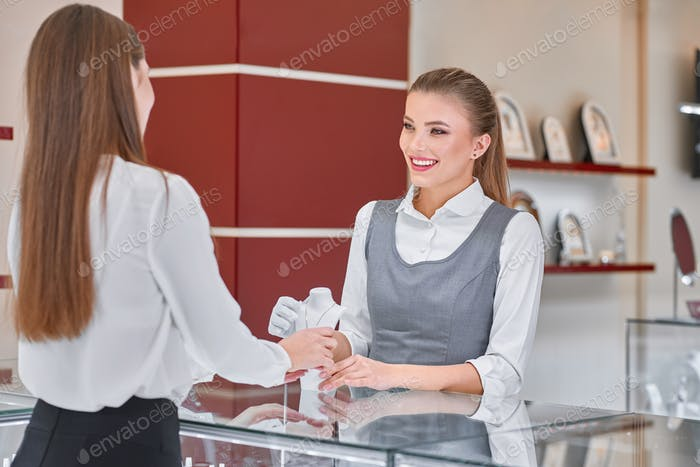 Young female jewelry worker helping to choose a necklace for a woman in a jewelry store