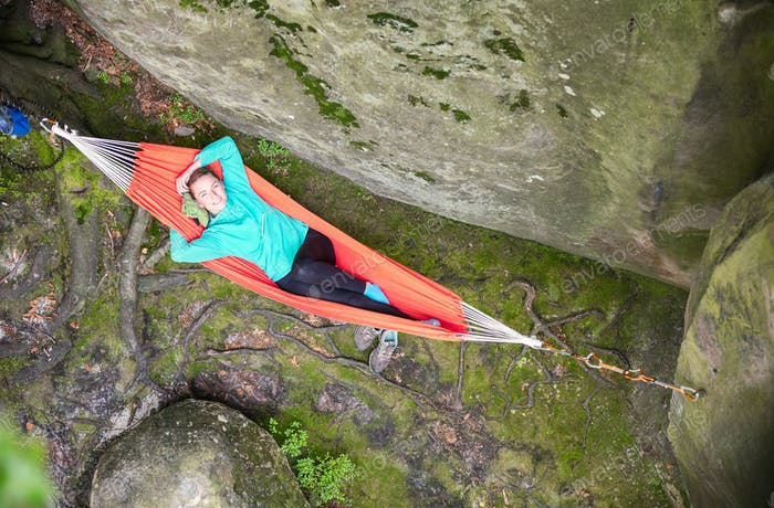 Cheerful young woman relaxing in hammock near cliff