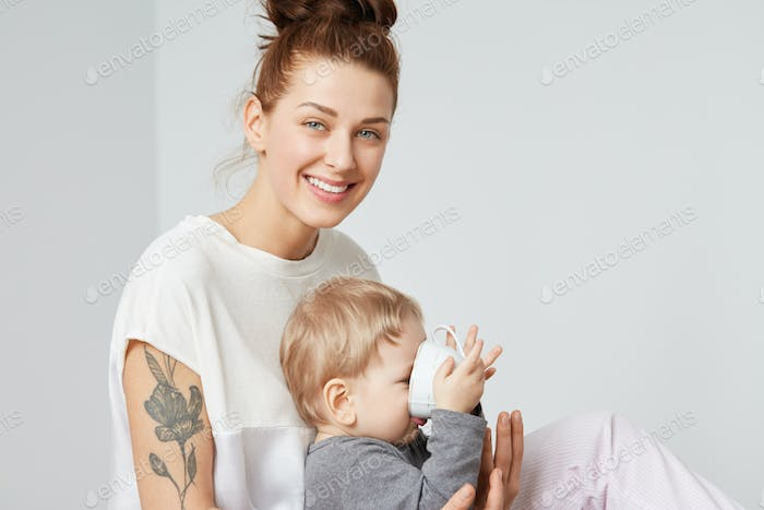 Family portrait of smiling modern mother and her infant on white background. Happy mom in white paja