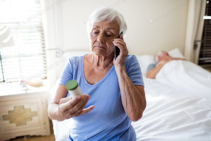 Woman talking on mobile phone and holding medicine prescription bottle in the bedroom