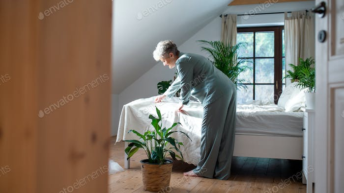 Senior woman in bed at home getting up in the morning, making a bed