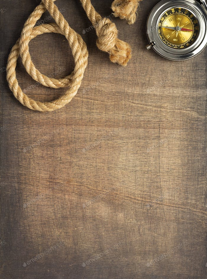 ship compass and rope at wooden background