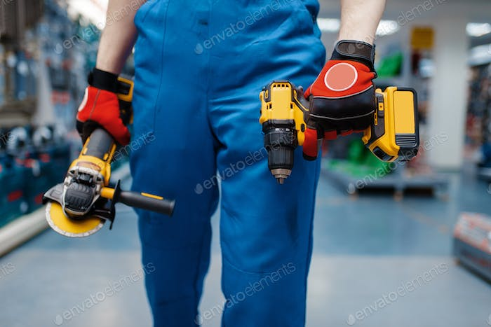 Worker holds battery screwdriver and angle grinder