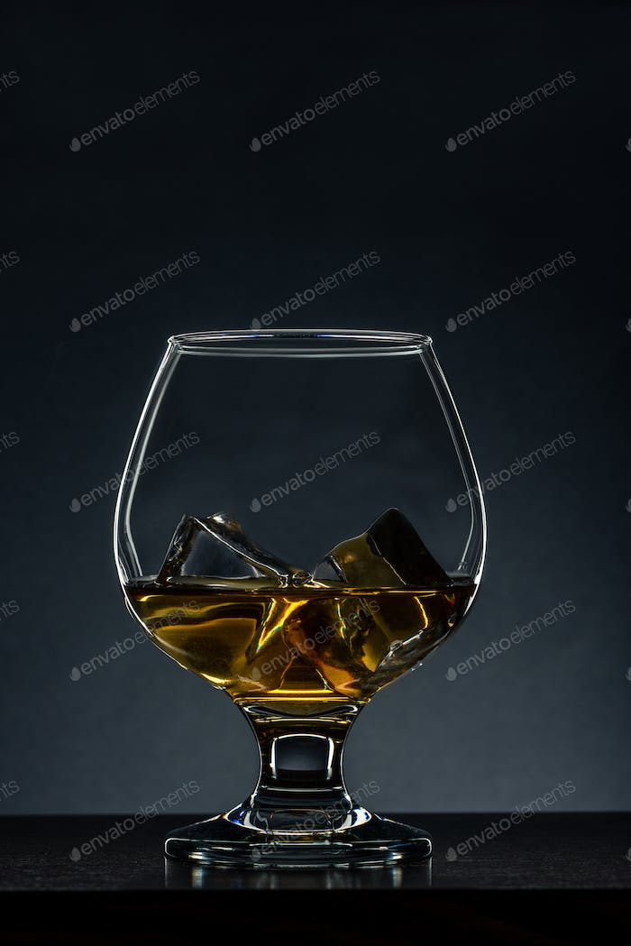 Elegant Glass with Cognac and Ice Cubes on Wooden Table. Copy Space Background