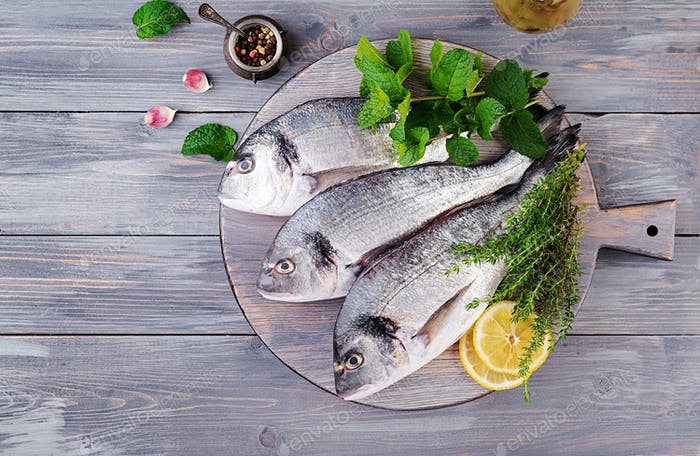 Raw dorado fish with green herbs cooking on cutting board. Top view