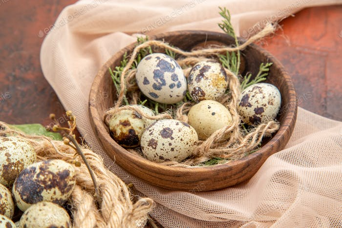 Top view of farm fresh eggs on a roll of rope on bag and on a pot on a brown table
