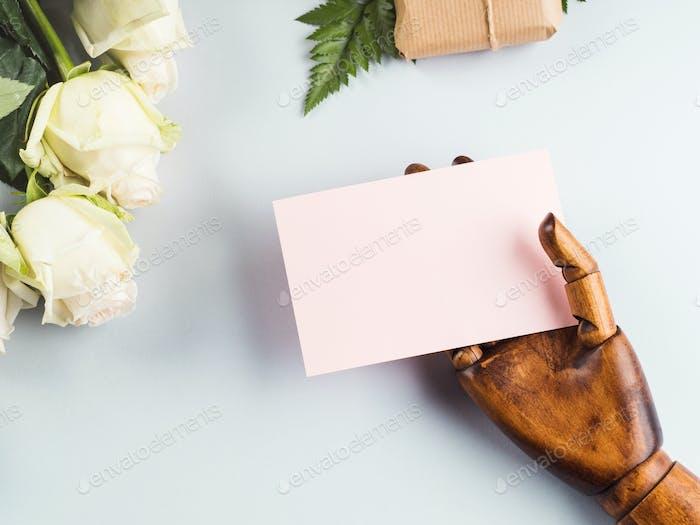 Weißer Rosenstrauß als Geschenk und Holzhand
