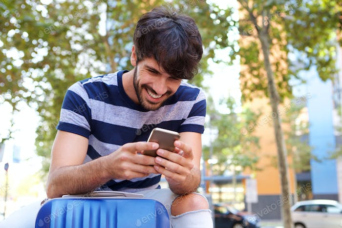 happy man sitting with mobile phone and suitcase
