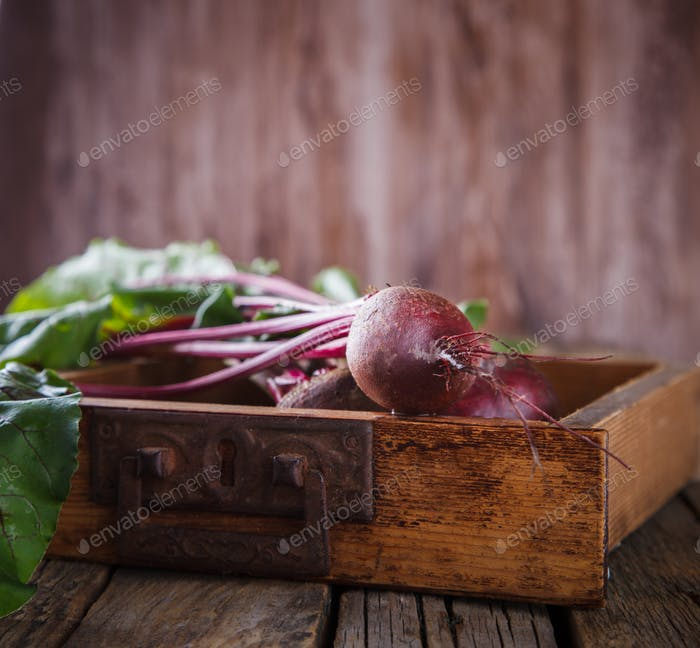 Young,fresh beets with tops on old wooden background.