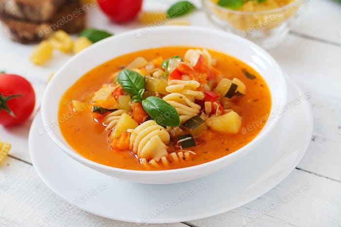 Minestrone, italienische Gemüsesuppe mit Pasta auf weißem Holztisch