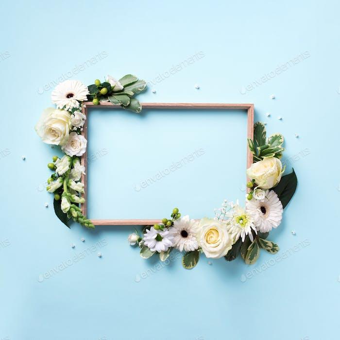 Rahmen aus weißen Blumen über blauem Hintergrund. Valentinstag, Frauentag-Konzept. Frühling oder Sommer