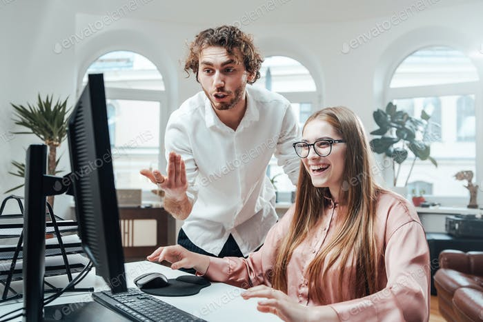 Woman laughs while her partner discuss something looking at screen