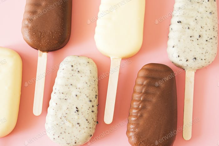 Line of milk and white chocolate popsicles on light pink background, top view