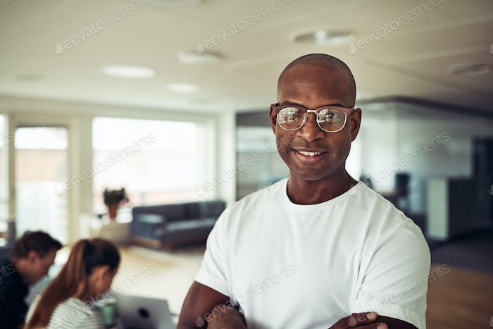 Confident African businessman smiling with colleagues in the background