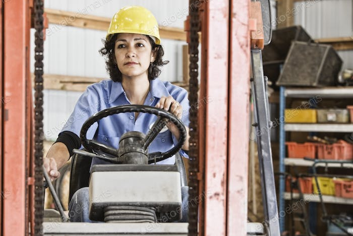 Hispanic woman employee using a forklift in a landscape company.
